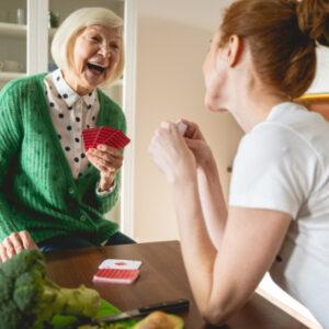 Seniorin, die mit einer jungen Frau Karten spielt.